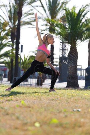 Photo pour Verticale pleine longueur de jeune coureuse femelle faisant l'exercice d'étirement avant a commencé sa course de matin à l'extérieur, femme caucasienne de forme avec la belle figure se réchauffant vers le haut dans le stationnement en jour ensoleillé d'été - image libre de droit