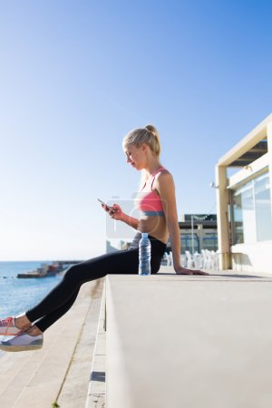 Fitness woman using her mobile phone