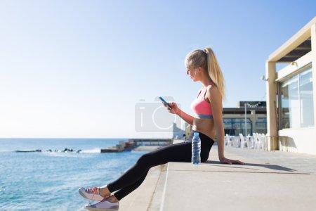Photo pour Belle jeune joggeuse profitant du repos après l'entraînement tout en bavardant sur son téléphone portable assis près de la mer contre un fond bleu ciel propre avec espace de copie pour votre message texte ou contenu - image libre de droit