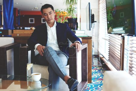 Photo pour Portrait d'un jeune directeur général à succès regardant les nouvelles à la télévision en attendant des partenaires d'affaires dans un restaurant moderne, homme d'affaires intelligent confiant se détendre dans le café pendant la pause luch - image libre de droit