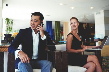 Photo for Smiling businesswoman looking at her male colleague while sitting with net-book in office, asian managing director having mobile phone conversation, professional employees preparing for the meeting - Royalty Free Image