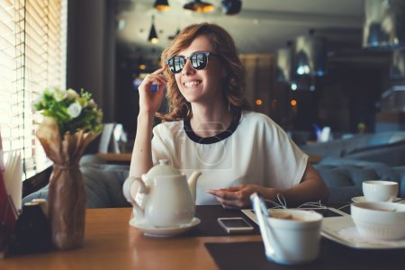 Photo for Portrait of attractive young woman smiling charmingly while looking out the window for her friends just arrived to the coffee shop where they meet,gorgeous female enjoying recreation time at breakfast - Royalty Free Image