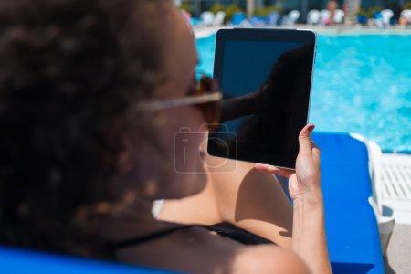 Woman in bikini holding touch pad