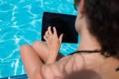 Femme en bikini avec pavé tactile près de la piscine