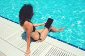 Female in bikini with touch pad near pool