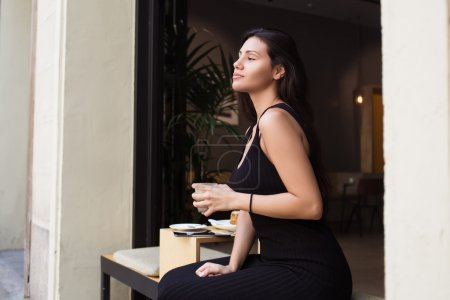 Photo pour Young latin woman enjoying rest after work day while sitting in sidewalk cafe, beautiful female tourist holding cup of drink while relaxing in coffee shop after active walking during summer vacations - image libre de droit