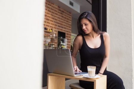 Photo pour Young female freelancer working on her laptop computer while sitting in modern coffee shop during lunch break in summer day, gorgeous latin woman connecting to wireless via net-book during breakfast - image libre de droit