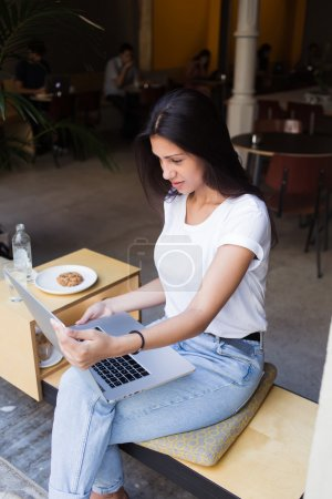 Young hipster girl working on her net-book