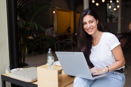 Photo pour Portrait d'une hipster girl souriante utilisant un ordinateur portable avec espace de copie pour votre message texte ou contenu publicitaire, charmante femme latine regardant de côté tout en tenant à genoux son net-book ouvert - image libre de droit