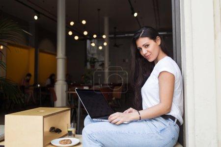 Photo pour Belle femme latine posant pour la caméra tout en travaillant sur son ordinateur portable pendant le petit déjeuner, charmante pigiste féminine utilisant net-book pour le travail à distance tout en étant assis dans un café de trottoir moderne - image libre de droit
