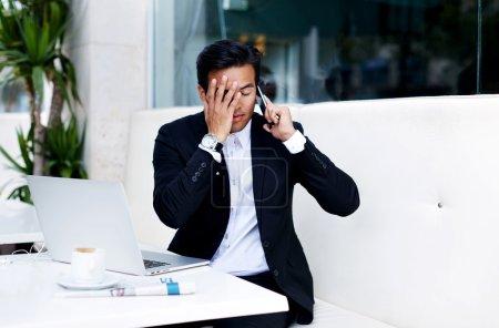 Worried businessman talking on mobile phone