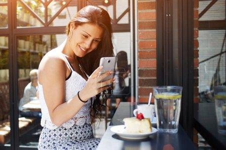 Photo pour Jeune jolie femme prenant des photos de son café petit déjeuner avec appareil photo de téléphone mobile, souriant magnifique femme latine photographiant gâteau avec des baies sur son téléphone portable, les gens utilisant la technologie - image libre de droit