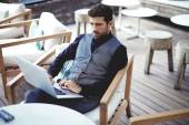 Businessman working on laptop at restaurant terrace