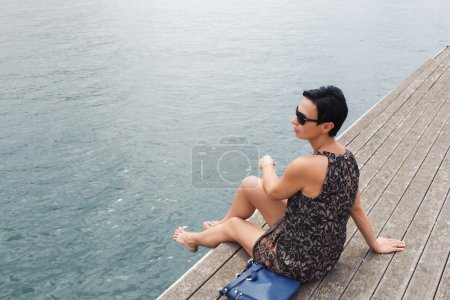 Attractive woman sitting on a wooden pier