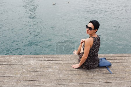 Woman sitting on the wooden pier near sea