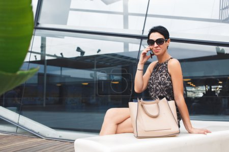 Photo for Portrait of successful businesswoman dressed in elegant clothes having mobile phone conversation while sitting near modern building in summer day, smiling female talking on her cellphone outdoors - Royalty Free Image