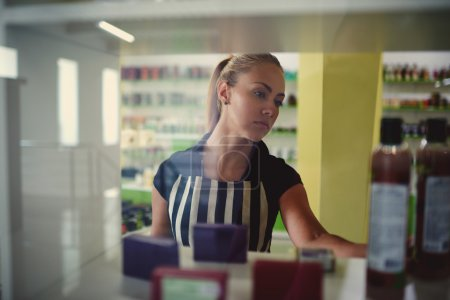 Photo pour Verticale d'une jeune femme choisissant des moyens hygiéniques dans la boutique de beauté, belle consultante de femme met des bouteilles de lotions tout en lisant l'information de produit dans l'intérieur de magasin de magasin ou de pharmacie de cosmétique - image libre de droit