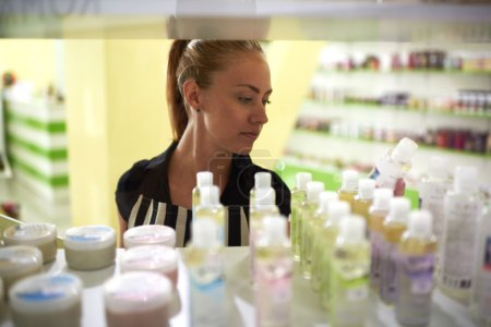 Female consultant recalculates cosmetic products