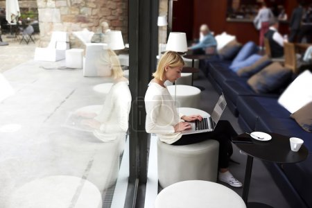 Woman working on net-book while sitting in cafe