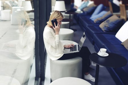 Woman with laptop talking on smartphone