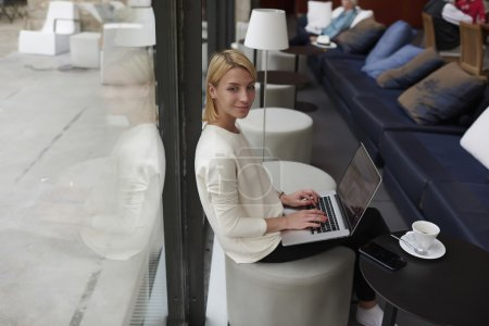 Woman working on net-book in cafe