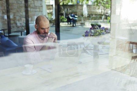 Businessman working on laptop in coffee shop