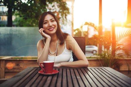 Photo pour Portrait d'une magnifique jeune femme asiatique heureuse assise dans un café confortable sur le trottoir souriant à la caméra, jolie femme profitant d'un après-midi ensoleillé dans un café moderne avec un coucher de soleil incroyable en été - image libre de droit