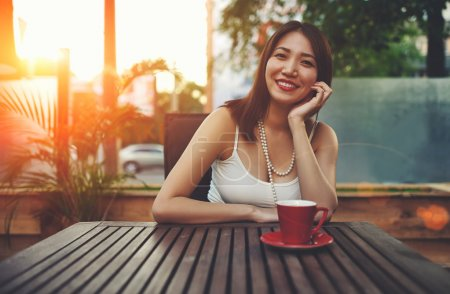 Smiling asian woman sitting in cafe