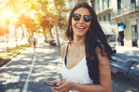 Photo pour Heureuse femme latine en lunettes de soleil d'été souriant tout en tenant smartphone se promener à l'extérieur dans la ville à la journée ensoleillée, personne féminine en utilisant mobile debout avec de l'espace de copie de composition sur un côté - image libre de droit