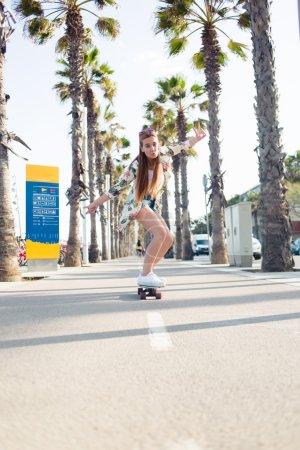 Stylish young female enjoying skating