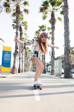 Stylish young female enjoying skating