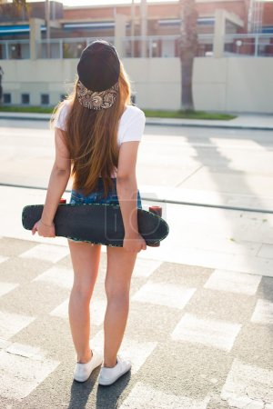 Stylish female  skateboarder standing on the street
