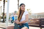 Woman skateboarder sitting  with penny board