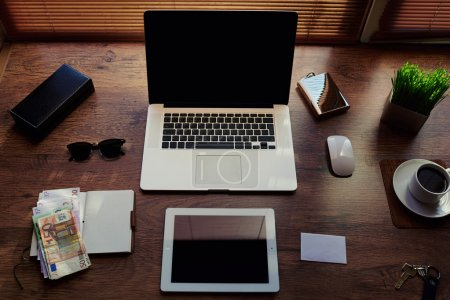 Photo for Mock up of successful person desktop with luxury accessories and distance work tools, portable laptop computer, digital tablet with blank copy space screen, money bills, notepad and cup of coffee - Royalty Free Image