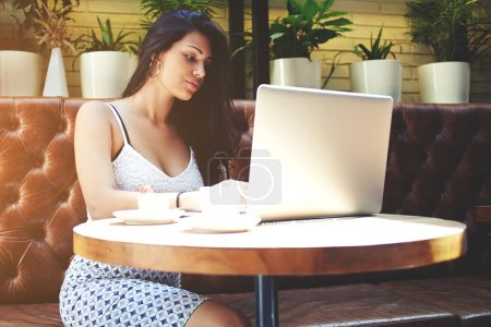 Woman working on laptop computer in cafe
