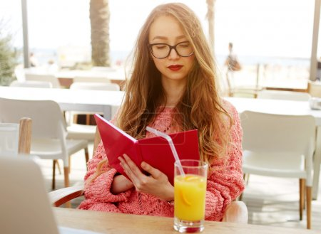 Female freelancer read notebook in cafe