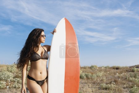Woman posing outdoors with her surfboard