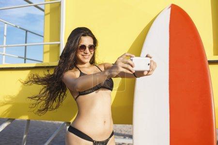 Woman in swimwear making self portrait
