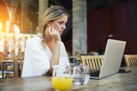 Photo pour Portrait de charmante jeune femme entrepreneur travailler sur ordinateur portable portable pendant la pause-café, magnifique pigiste femme en utilisant net-book pour le travail à distance tout en étant assis dans l'intérieur du café bar moderne - image libre de droit