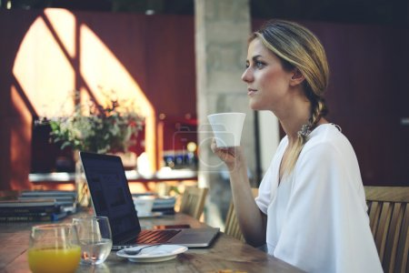 Woman resting after work on laptop in cafe