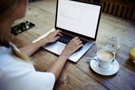 Photo pour Vue arrière du pigiste créatif féminin assis ordinateur portable avant avec écran espace exemplaire est pour votre information, entreprise jeune femme travail sur net-livre pendant le petit déjeuner au café-restaurant moderne - image libre de droit