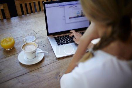 Photo pour Vue prise de vue recadrée de la jeune femme travaillant sur ordinateur portable tout en étant assis dans l'intérieur du café bar moderne, blonde pigiste utilisant net-book pour le travail à distance pendant le petit déjeuner du matin dans un café - image libre de droit