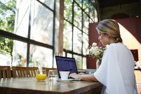 Photo for Portrait of a young female student using portable laptop computer while work at the coursework, blonde woman sitting at the table with open net-book in coffee shop interior during morning breakfast - Royalty Free Image