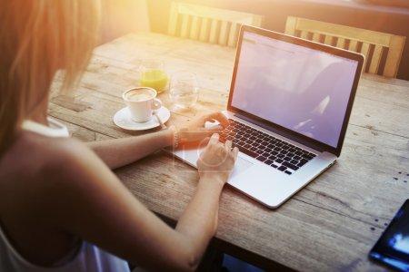 Photo pour Vue prise de vue recadrée de la jeune femme au clavier sur un ordinateur portable avec écran d'espace de copie vierge alors qu'elle était assise dans un café, étudiante blonde travaillant sur le net-book après ses conférences à l'université, soleil torride - image libre de droit