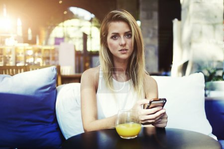 Woman using mobile phone during breakfast