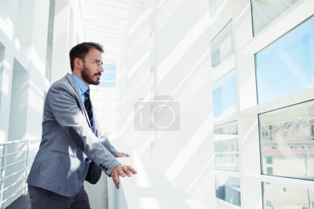 Photo pour Portrait d'un homme entrepreneur vêtu de vêtements de luxe coûteux regardant dans la fenêtre du bureau pendant le repos après le briefing, homme intelligent directeur général pensant à quelque chose pendant le repos après le travail - image libre de droit