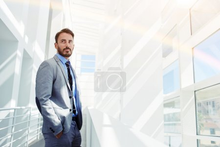 Photo for Successful man manager dressed in expensive corporate clothes standing in modern office building with copy space, successful intelligent man in luxury suit resting after business meeting with partners - Royalty Free Image