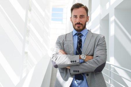 Photo pour Portrait de jeune homme intelligent avocat debout avec les bras croisés dans l'intérieur de l'immeuble de bureaux moderne, employé de banque mâle réussi habillé en costume de luxe posant avec espace de copie pour votre texte - image libre de droit