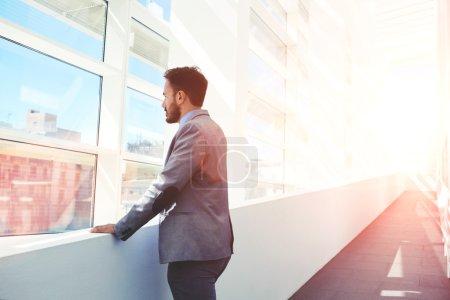 Photo pour Homme intelligent dans l'usure formelle regardant dans une grande fenêtre de bureau - image libre de droit