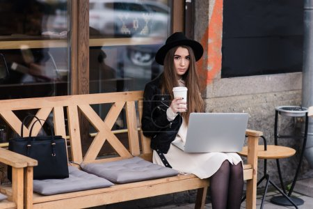Young woman working on net-book in cafe